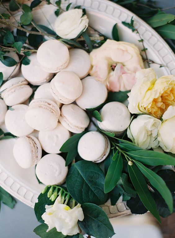 white macarons displayed on a dish with greenery and flowers