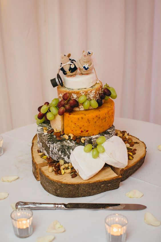 a cheese tower with grapes and mouse cake topeprs for fun