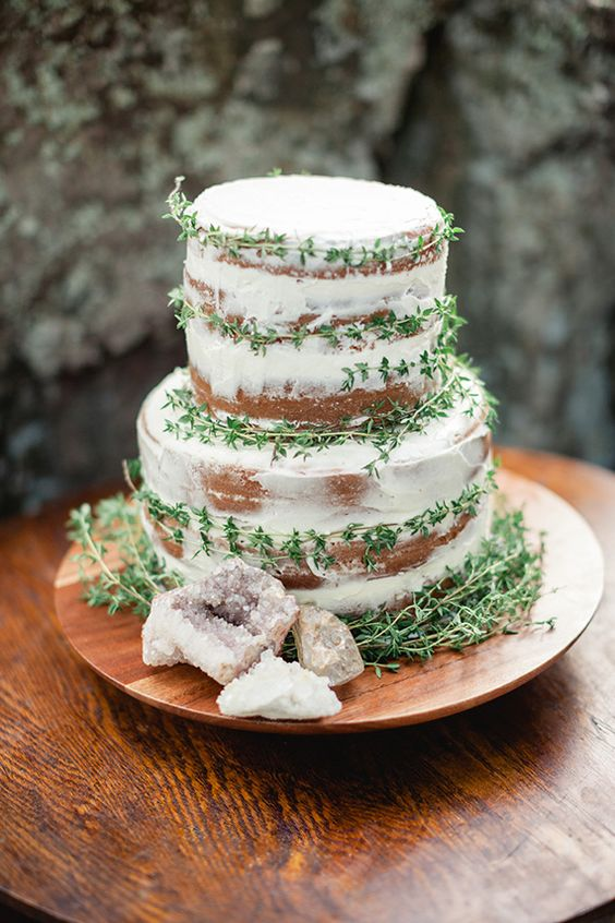 a naked wedding cake with fresh greenery and agate slices