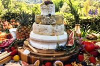a cheese tower for a tropical wedding displayed with fresh fruit, berries and crackers
