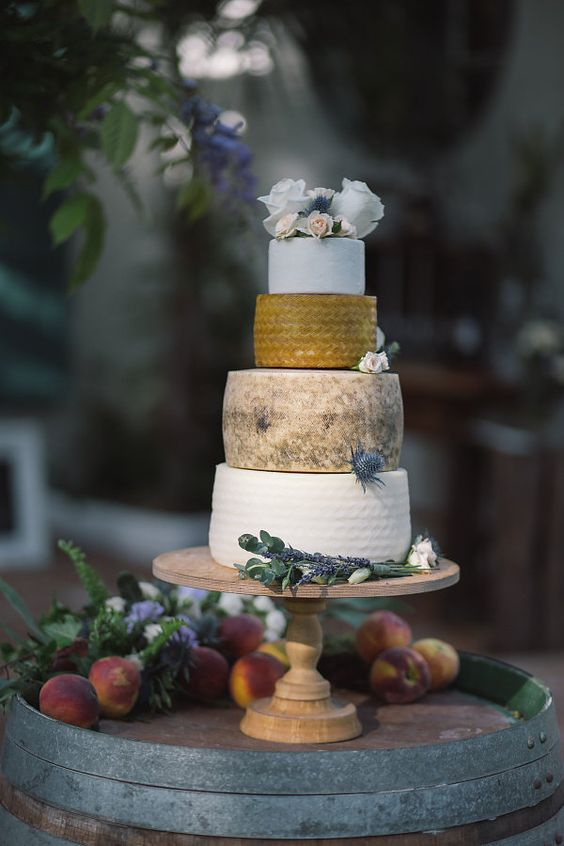 a cheese tower on a wooden stand and fresh blooms and thistles