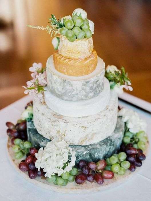 a cheese tower with fresh grapes all over and some blooms