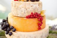 a cheese wheel cake with grapes, figs put on fresh lavender