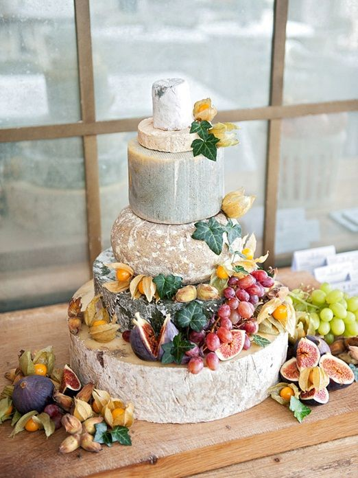 a chic and natural cheese tower with leaves, grapes and figs