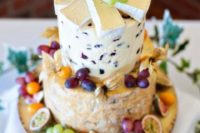 a cute and small cheese tower with fresh grapes