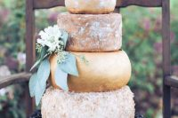 a huge cheese tower with greenery and flowers and some cherries for displaying