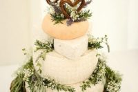 a wild and natural cheese wedding cake decorated with garden grown lavender and herbs, wicker letter toppers