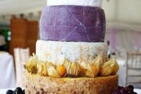 bold cheese tower with grapes and figs on a wooden stand