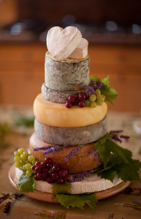 cheese tower instead of a wedding cake, topped with grapes and lavender, cheese hearts instead of toppers