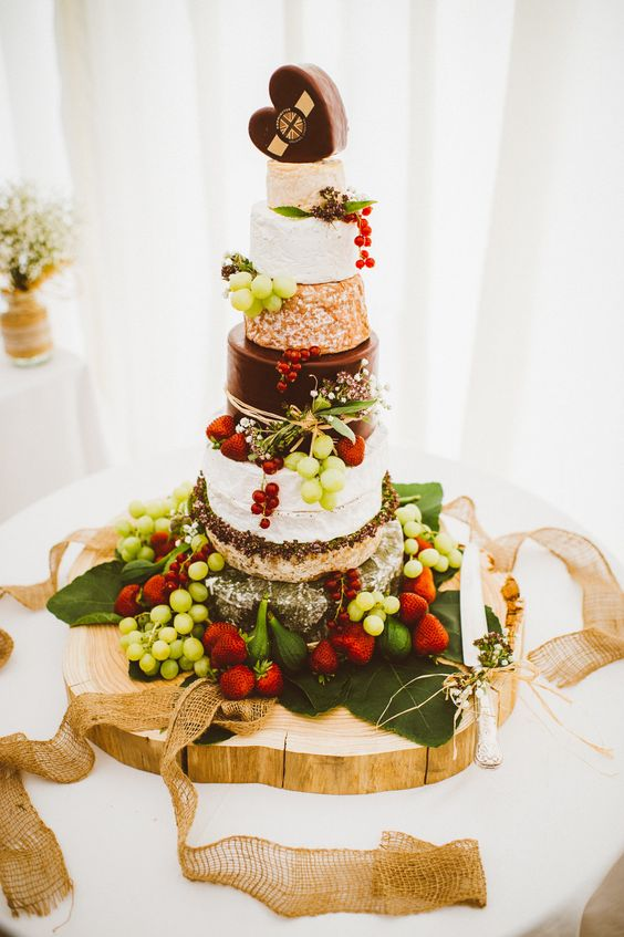 cheese wheel cake with fresh grapes, strawberries placed on a palm leaf