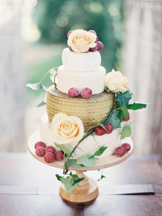 chic cheese wheel tower with grapes and peachy blooms on a wooden stand