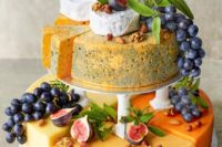 large cheese tower with figs and grapes, some leaves for decor
