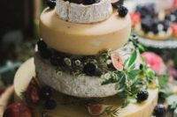 rustic cheese display with a wooden slice, blackberries, figs and cherries