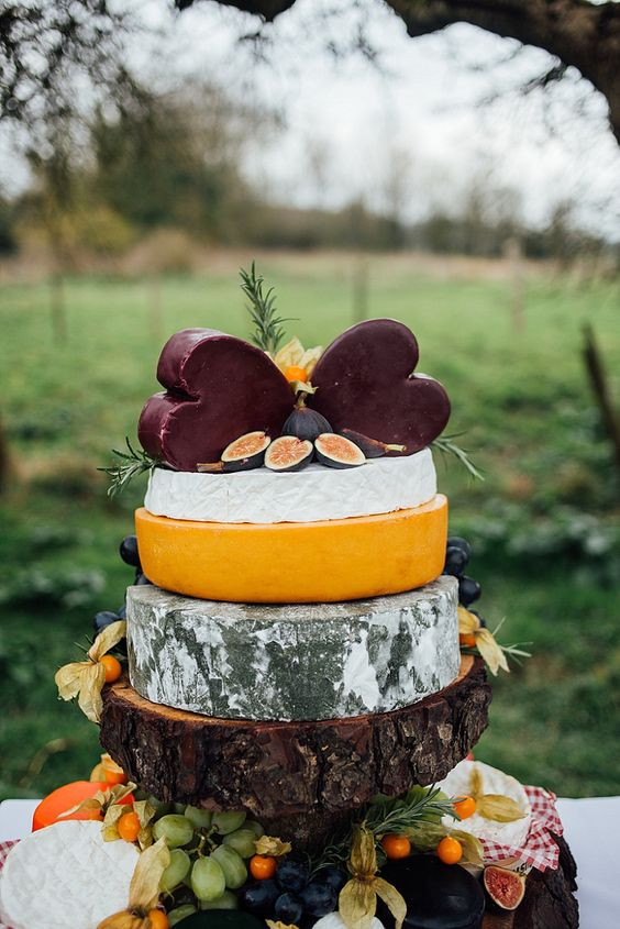 rustic cheese tower on a thick wooden piece with herbs and figs