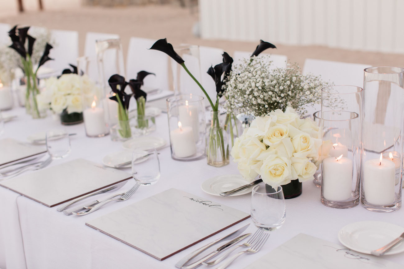 This is a tablescape for the rehearsal dinner, baby's breath and white roses contrast with black callas