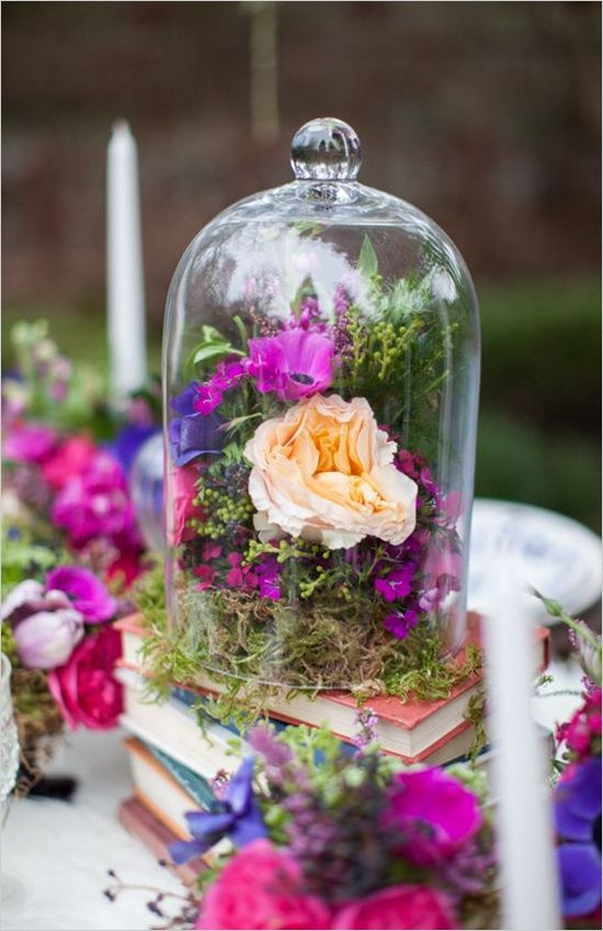 a centerpiece with moss and bold blooms put on a tack of books