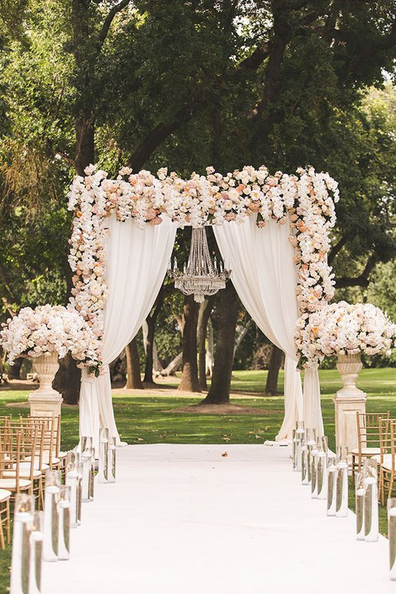 a refined wedding arch with blush flowers, white curtains and a glam chandelier