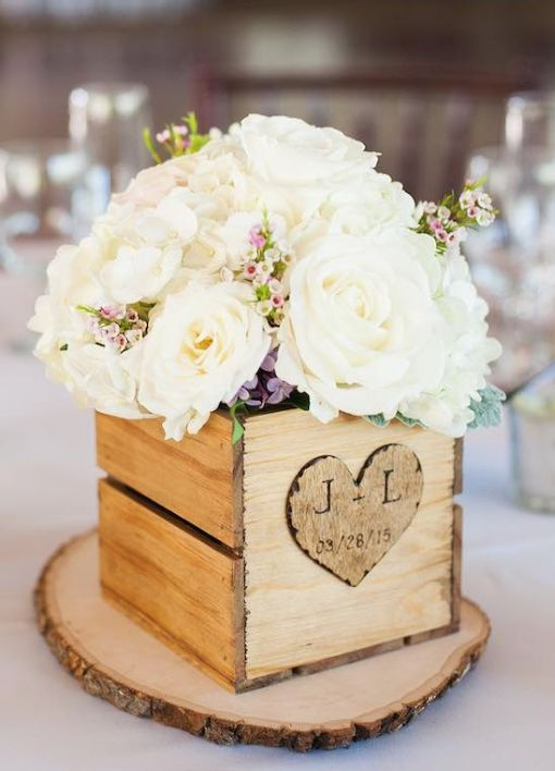 a wooden box with a wood burnt heart and white blooms on a wooden slice