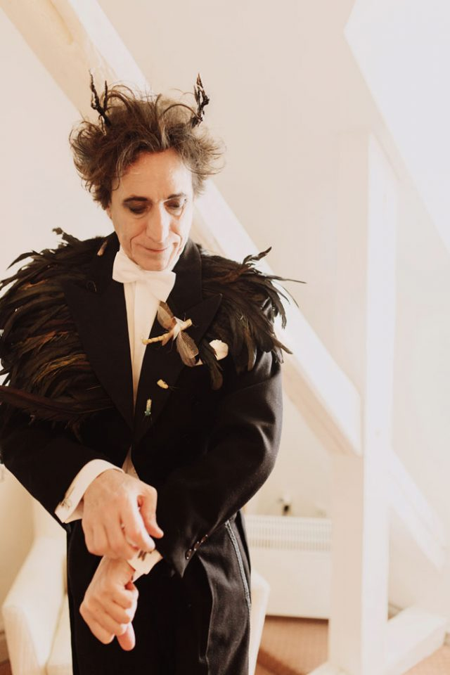 The groom's suit was customized with feathers by the bride, and he also wore tiny antlers