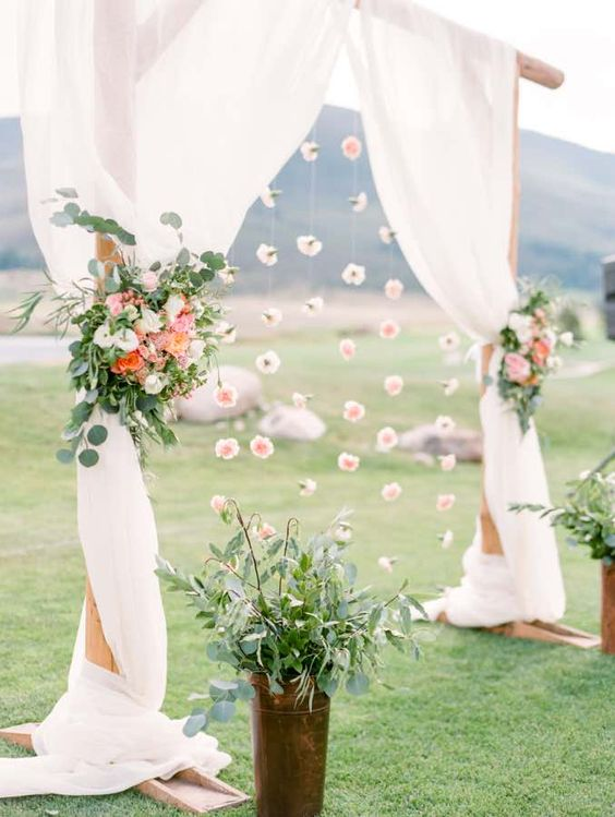 a wooden arch with flowy curtains, hanging blooms and floral posies