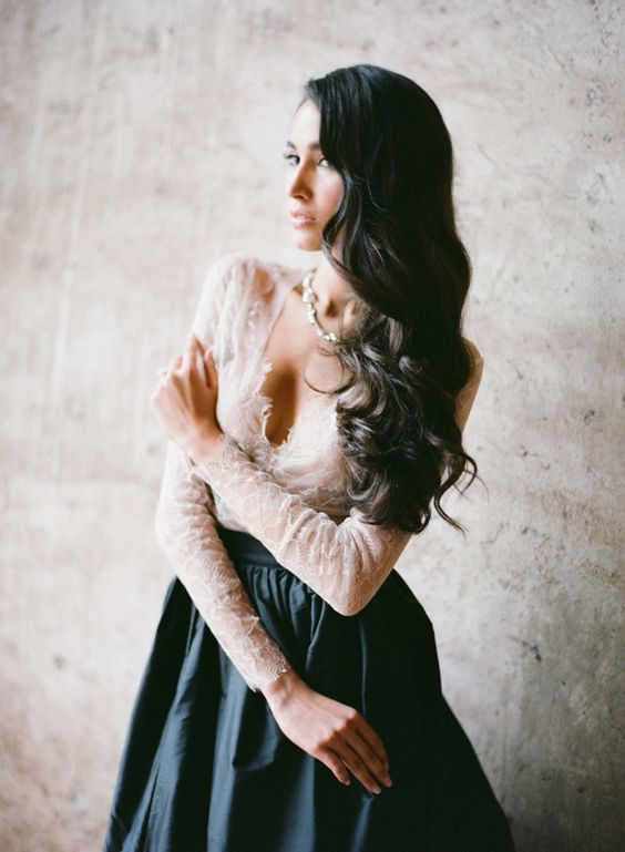 an ivory lace top with a V neckline and long sleeves and a black skirt