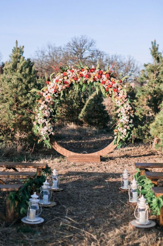 giant floral wreath wedding backdrop in red and blush tones for a winter ceremony