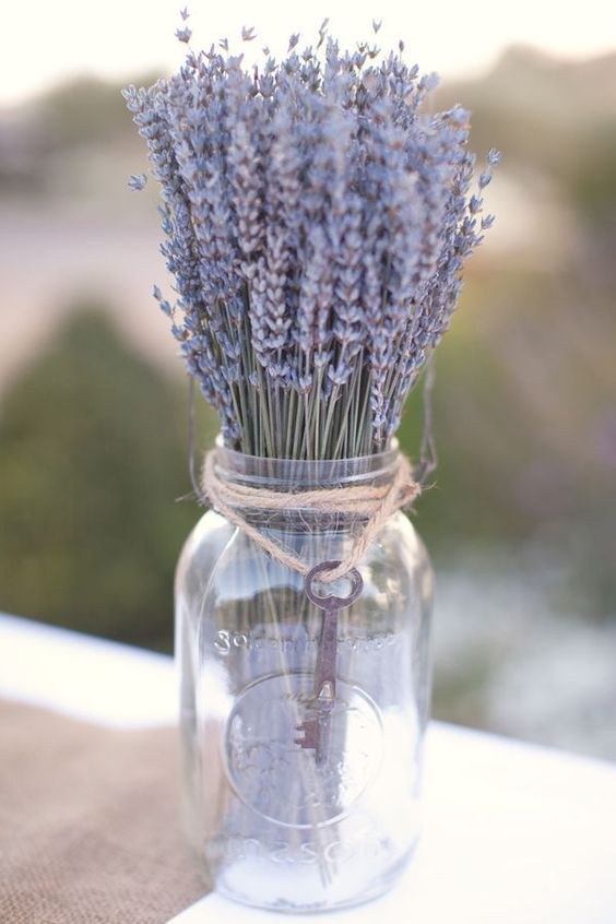 a clear mason jar with lavender and a vintage key for a refined centerpiece