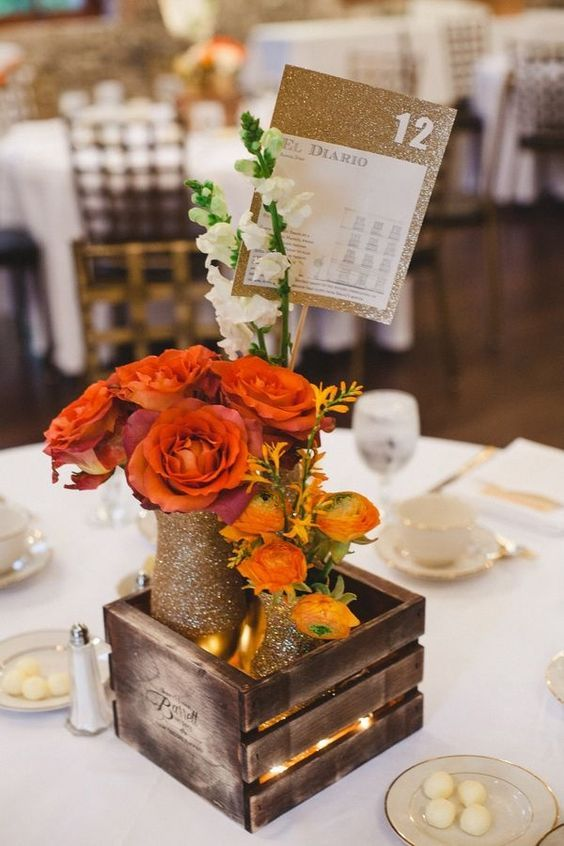 a crate with bold orange and red blooms, glittered vases