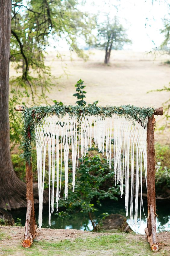 a rustic log arch with crochet lace and greenery for a camp ceremony