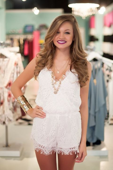 a white lace romper with spahetti straps and layered necklaces