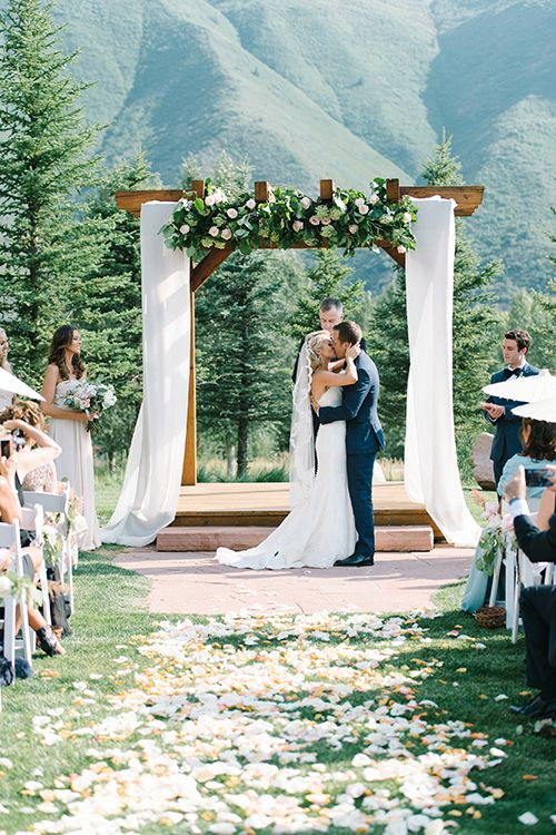 a wooden chuppah with flowy white fabric, blush flowers and greenery