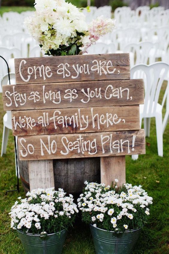 a wooden sign and buckets with white flowers