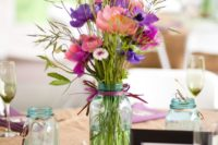 05 a clear mason jar with purple and pink flowers