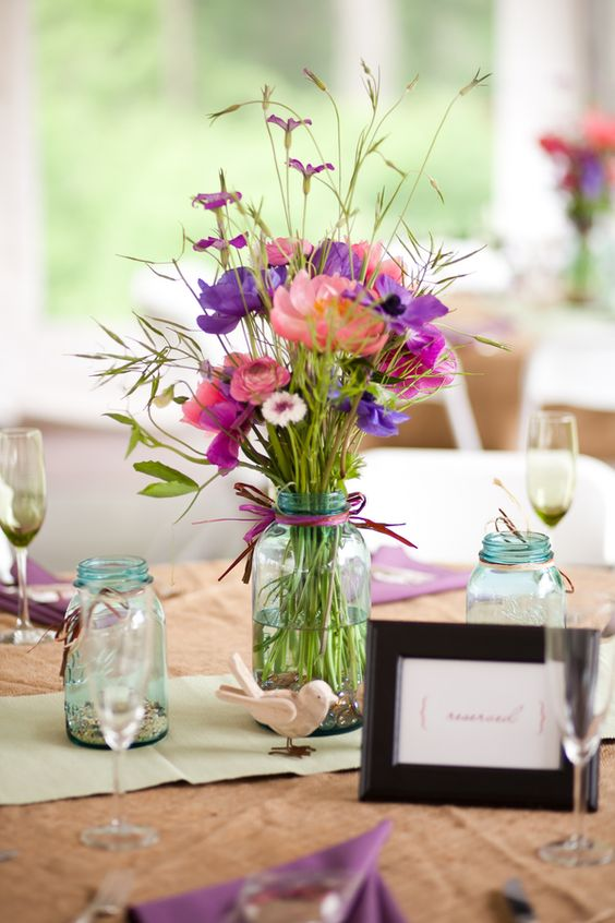 a clear mason jar with purple and pink flowers