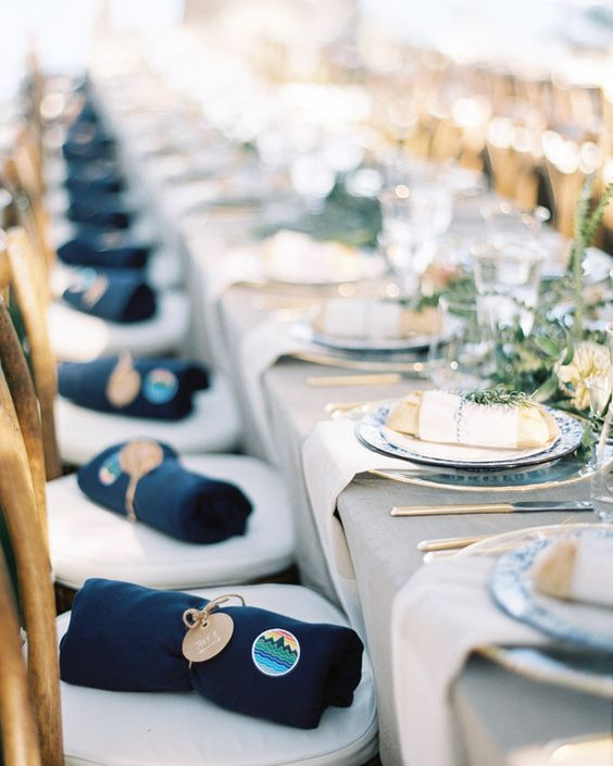 a wedding table setting in the shades of grey, blue and green and blankets for the guests