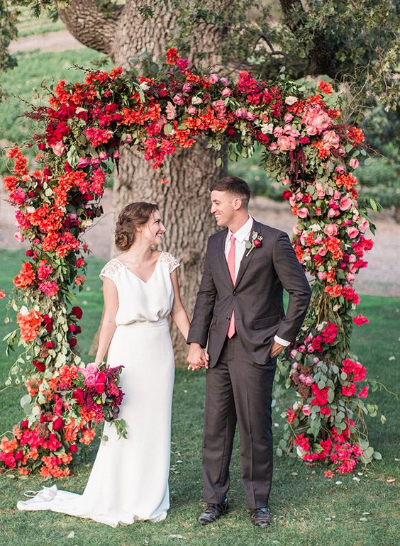 bold red and fuchsia flower wedding arch