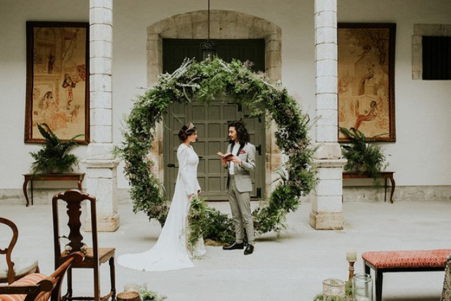 The wedding backdrop was an oversized greenery wreath, which is a popular trend today