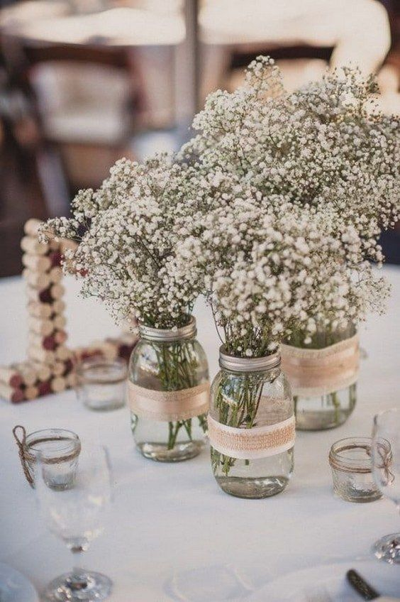 a combo of three mason jars wrapped with burlap and with baby's breath