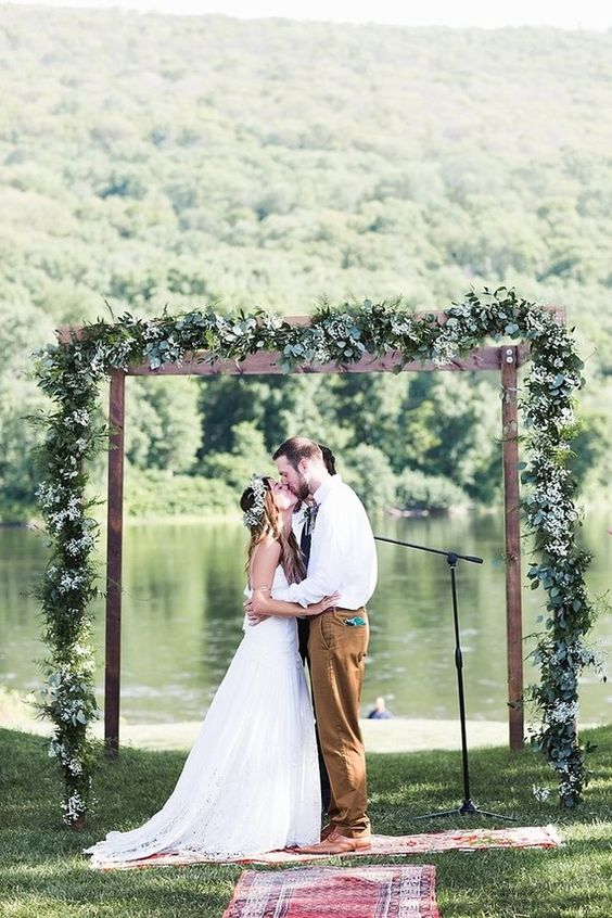 a woden arch covered with a greenery garland and a lace behind for a perfect backdrop