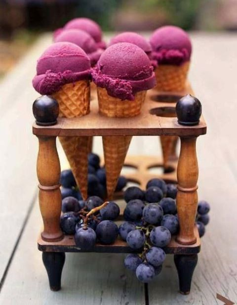 black raspberry ice cream served on a wooden stand and fresh grapes