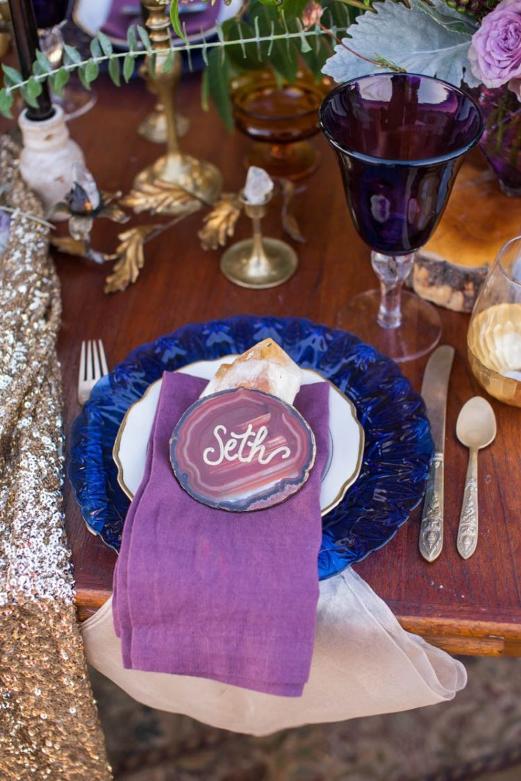 The wedding table setting was deccorated with bold blue plates, purple glasses and of course stone slices