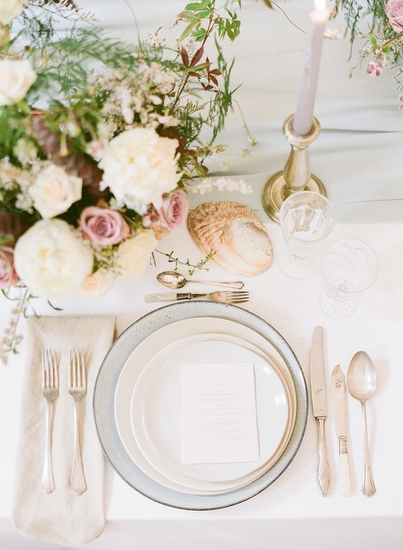 The wedidng table setting was with a light grey runner, gilded candle holders and even shells