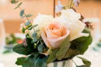 07 a bucket with greenery and blush roses plus a wooden table number on a skewer