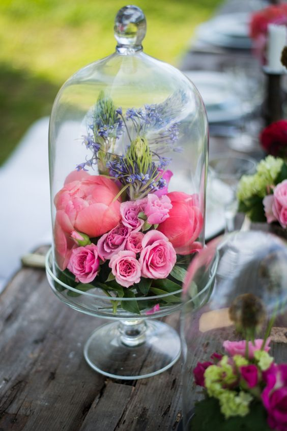a cloche with fresh blooms in pink and purple
