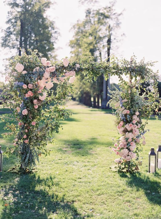gorgeous wedding arch with pink roses, lilac flowers and greenery