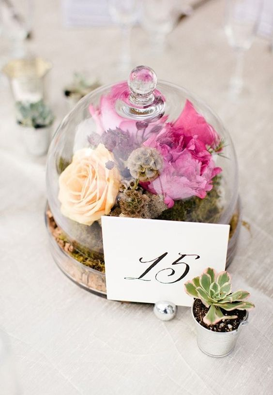 a cloche with moss and bold flowers, a paper table number attached