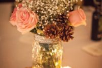 08 a glittered wood slice with a table number, candles and a mason jar with baby's breath, roses and pinecones