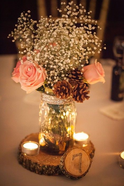 a glittered wood slice with a table number, candles and a mason jar with baby's breath, roses and pinecones