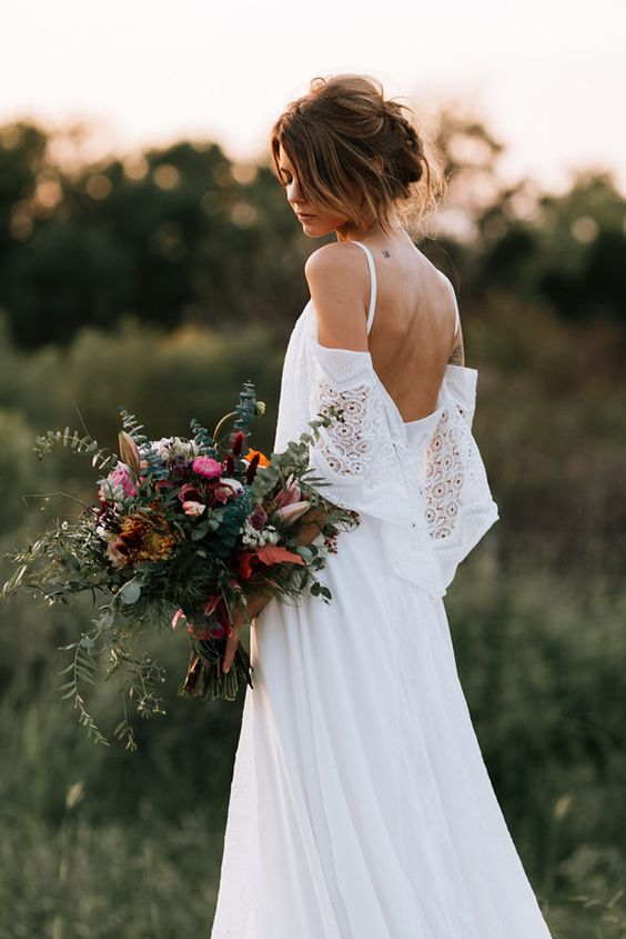 a moody bouquet with eucalyptus, bold blooms and feathers