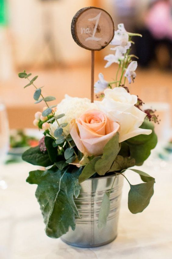 a bucket with blush and white roses, leaves and eucalyptus, a wood slice table number
